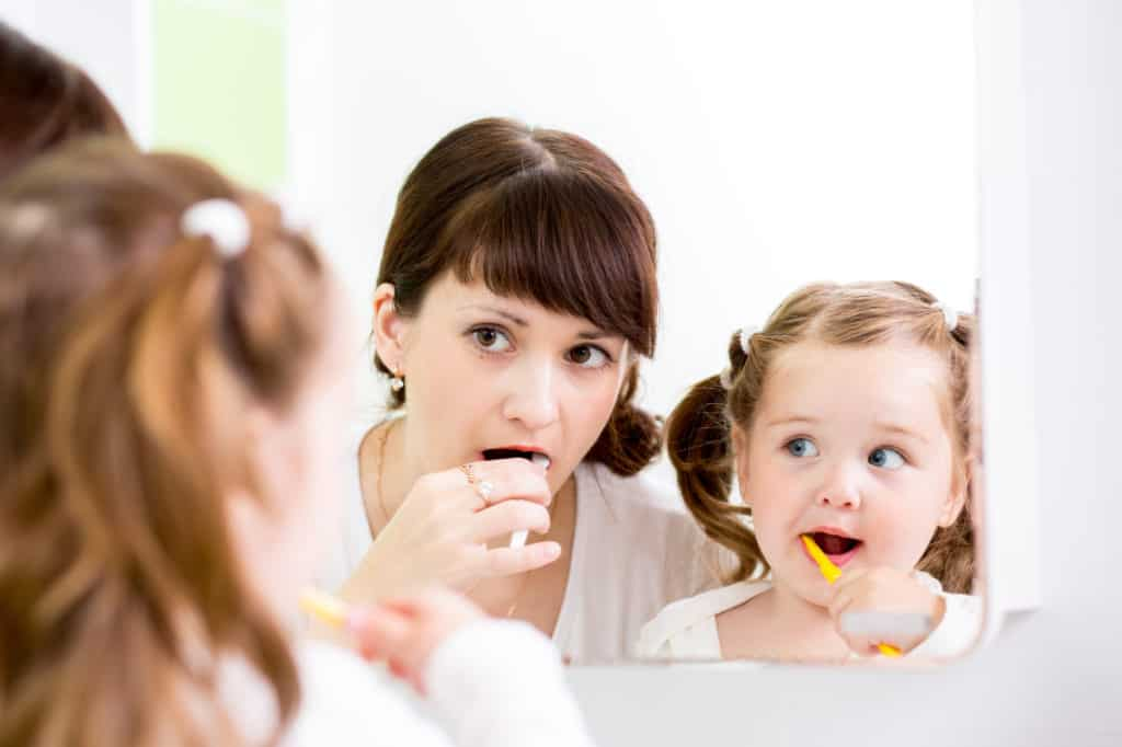 Kid and Parent Brushing Teeth